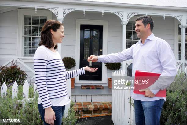 Happy real estate agent man gives keys to a new home owner woman