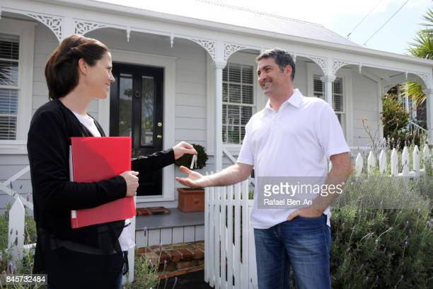 happy real estate agent woman giving keys to a new home owner man - rafael ben ari imagens e fotografias de stock