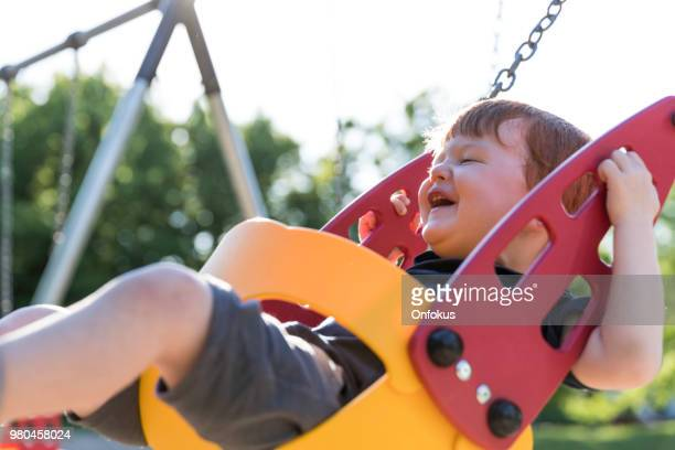 Happy Redhead Toddler Boy Sitting in Playground Swing Outdoors
