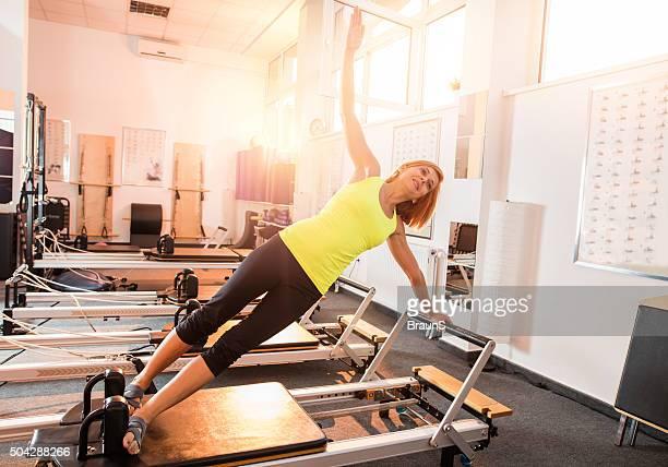 Glücklich Rotes Haar Frau Trainieren Sie an einem Pilates-Gerät im Fitnessstudio.