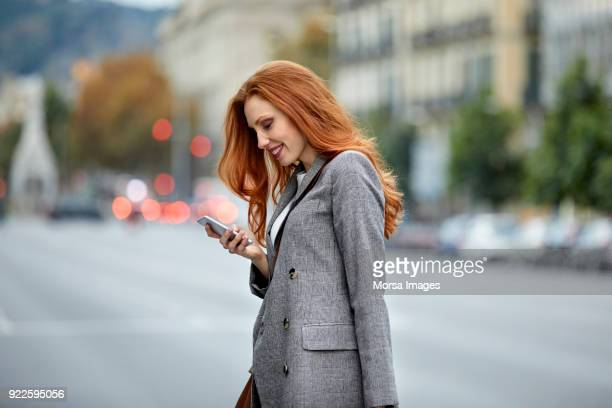happy redhead woman using smart phone in city - gray blazer stock pictures, royalty-free photos & images