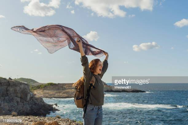 happy redheaded young woman holding a cloth at the coast, ibiza, spain - islas baleares fotografías e imágenes de stock