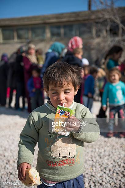 Happy refugee boy with orange juice and sandwich