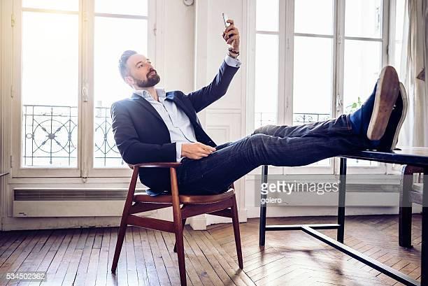 Heureux homme d'affaires détendue prenant selfie à Domicile Bureau