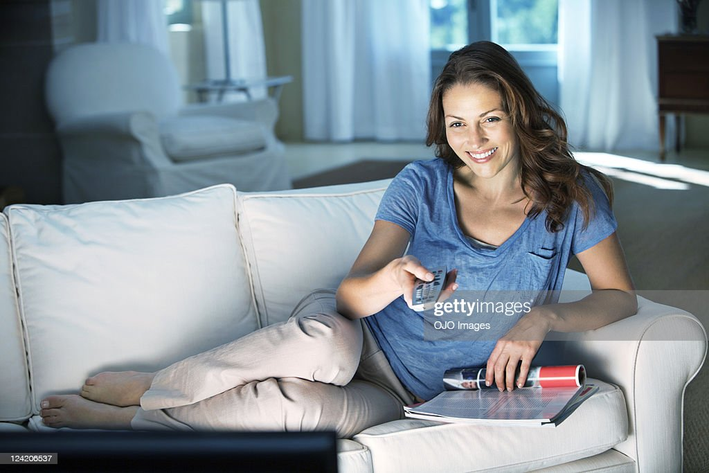 Happy relaxed mid adult woman holding remote control at home : Stock Photo