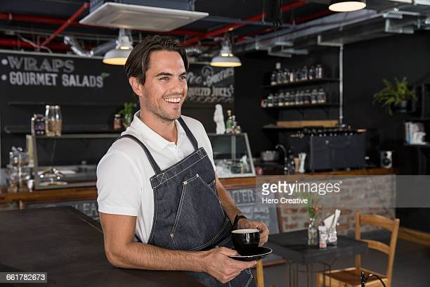 Happy restaurateur taking coffee break
