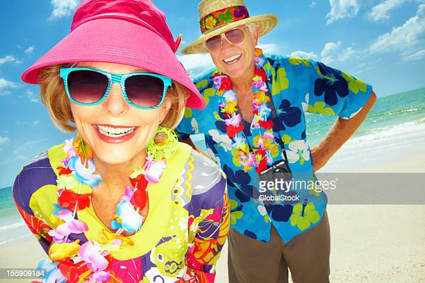happy retired couple vacationing at the beach  - multi colored hat stock pictures, royalty-free photos & images