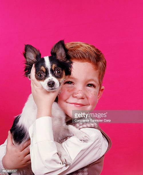 Happy retro boy with freckles holding puppy