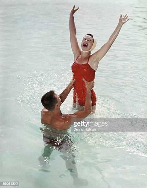 Happy retro couple jumping and splashing in water