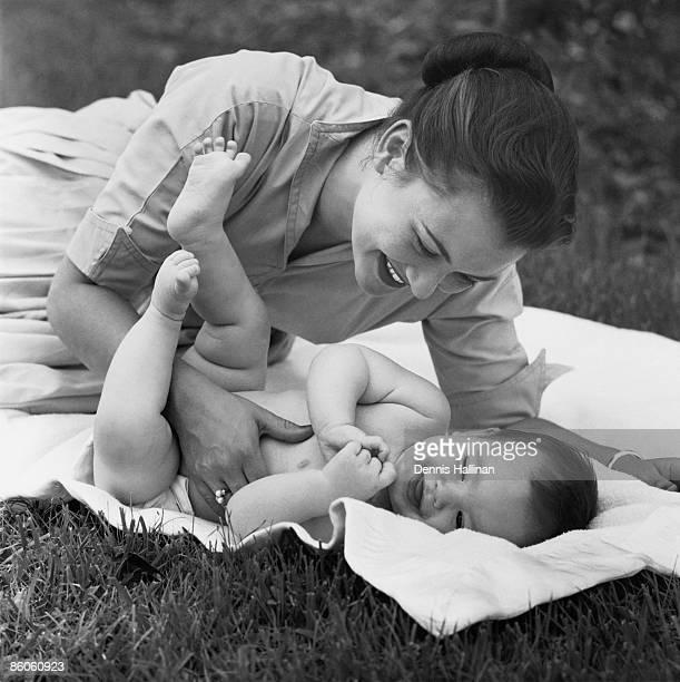 Happy retro mother and baby lying on blanket in backyard