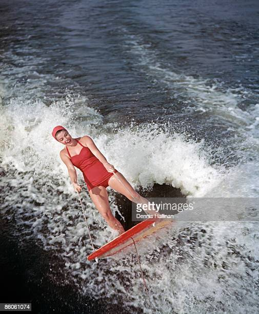 Happy retro water skier riding water sled