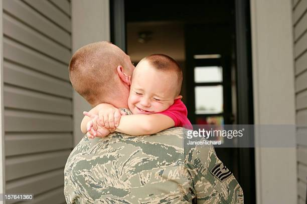 Happy return of military father holding his son