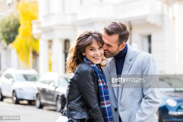 happy romantic couple flirting in the city street - gray coat stock pictures, royalty-free photos & images