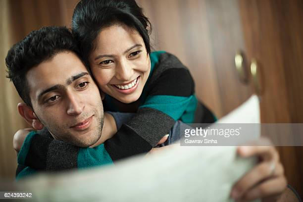 Happy romantic couple reading newspaper together.