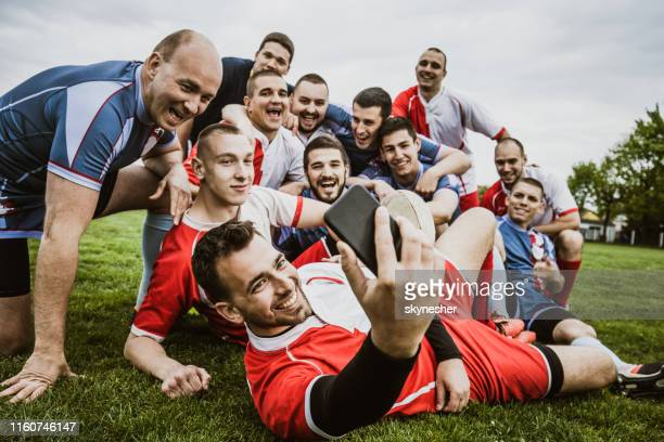 happy rugby players taking a selfie with cell phone on a playing field. - sports league stock pictures, royalty-free photos & images