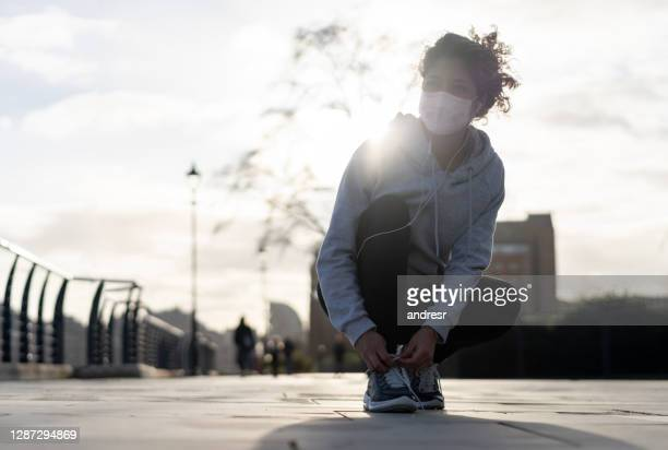 happy runner tying her shoelaces outdoors and wearing a facemask - state of emergency stock pictures, royalty-free photos & images