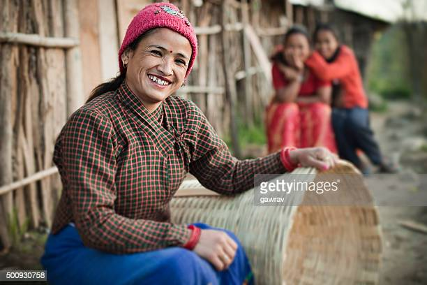 happy rural asian woman looking at camera, sitting near hut. - nepalese ethnicity stock pictures, royalty-free photos & images