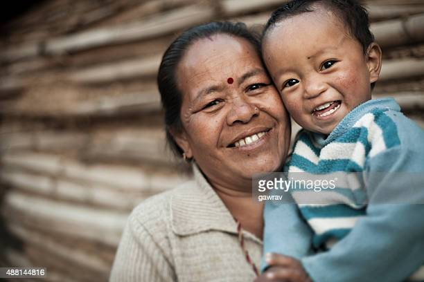 Happy rural mature Asian woman with grandson giving toothy smile.