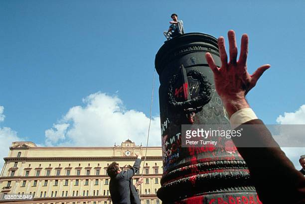 Happy Russian demonstrators vandalize the pedestal of the statue of the modern KGB's founder following the failed coup attempt