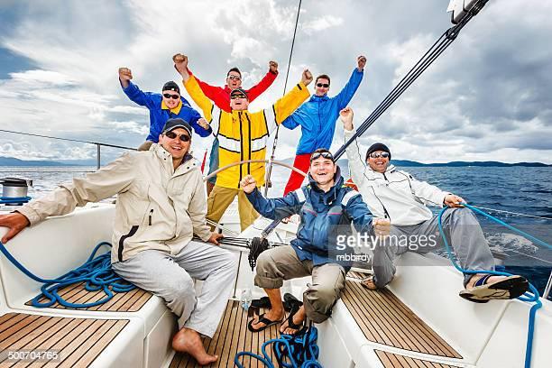 Happy sailing crew on sailboat