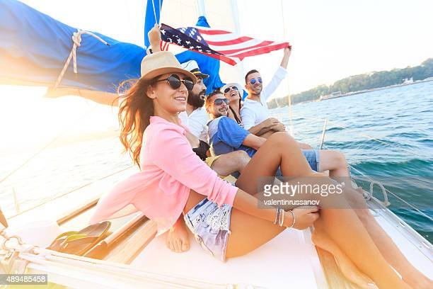 happy sailing crew on sailboat with american flag - american flag ocean stock pictures, royalty-free photos & images