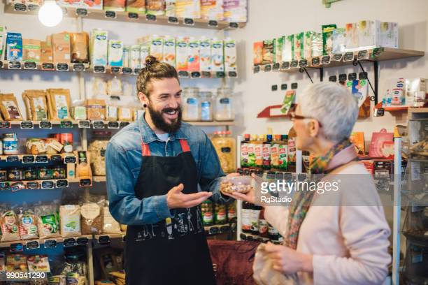 happy sales man handing a pack of nuts to a customer - salesman stock pictures, royalty-free photos & images