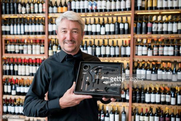 Happy salesman showing a box with wine accesories