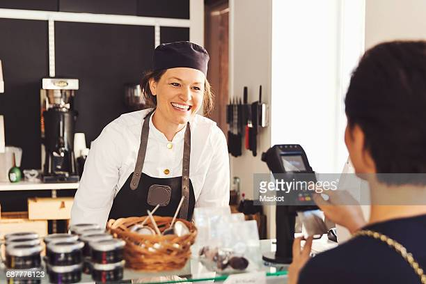 Happy saleswoman looking at female customer entering pin in credit card reader at grocery store