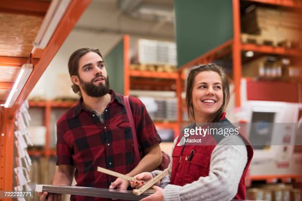 Happy saleswoman looking away while standing with male customer in hardware store