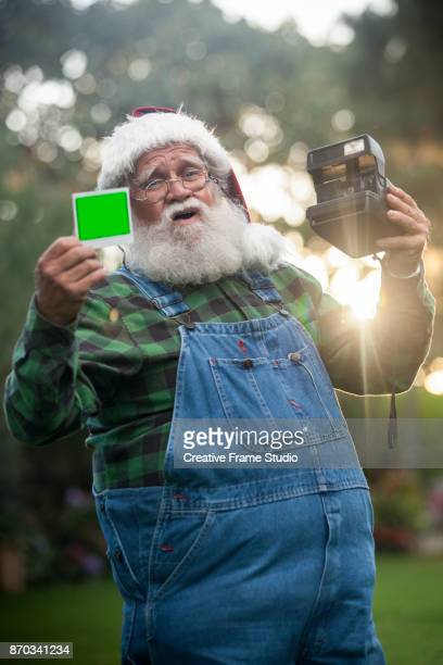Happy Santa Claus showing a photo taken with an instant camera