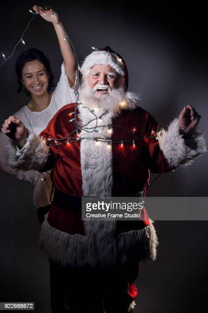 happy santa claus untied / untangled from christmas lights helped by a smiling woman - pere noel libre de droit photos et images de collection