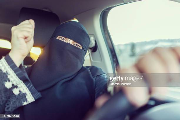 Happy Saudi Arabian woman celebrating victory by getting licence for driving car
