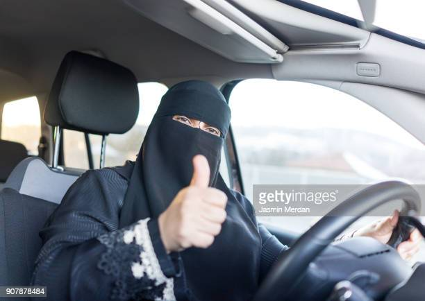 Happy Saudi Arabian woman driving a car