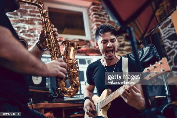 happy sax player and guitarist performing song together - performance group stock pictures, royalty-free photos & images