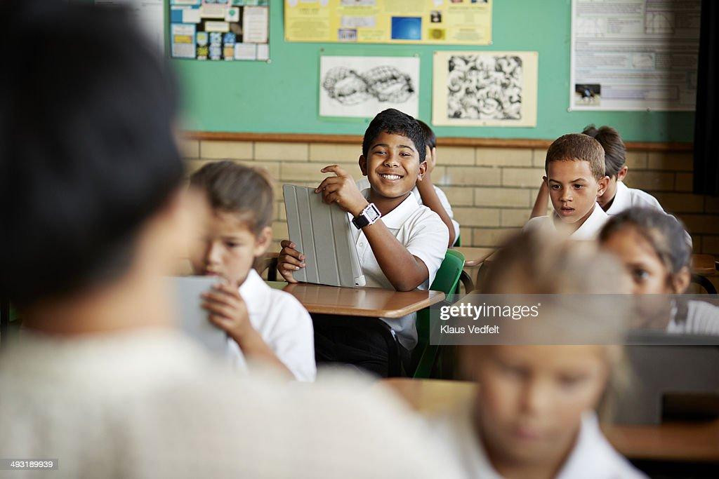 Happy school boy among classmates : Stock Photo