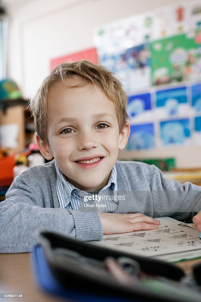 Happy school boy (8-9) sitting in class room : Stock Photo