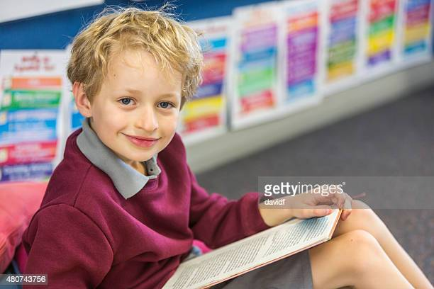 Happy School Boy Sitting Reading a Book