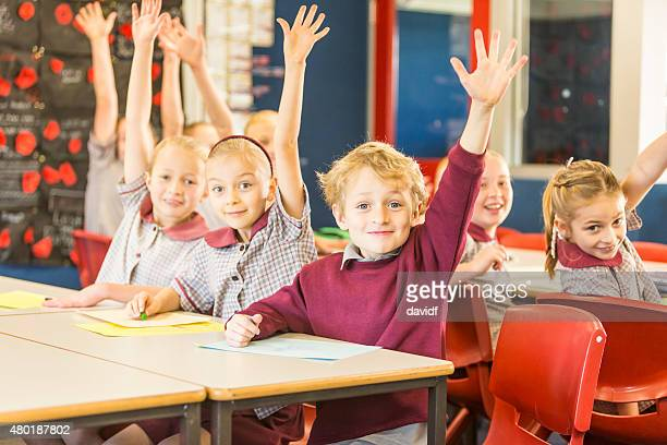 Happy School Children Answering a Question in the Classroom