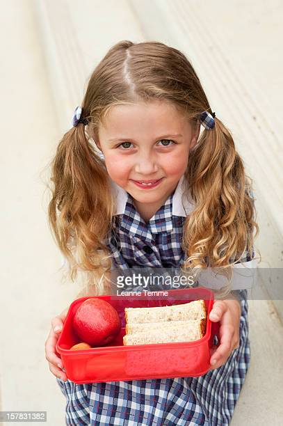 Happy school girl holding a red lunch box outside