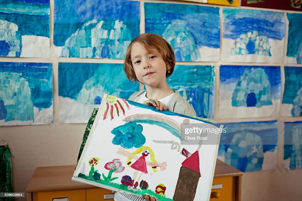 Happy school girl (6-7) showing her painting : Foto de stock