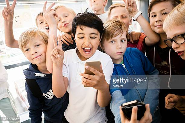 Happy school kids using mobile phone with peace sign in corridor