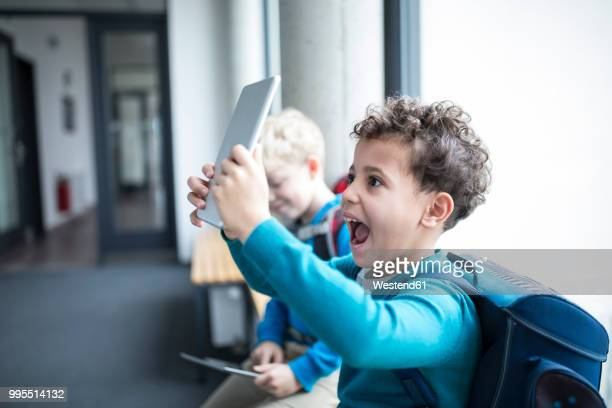 Happy schoolboy holding up tablet on corridor in school