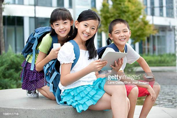 Happy schoolchildren with high-tech digital gadgets