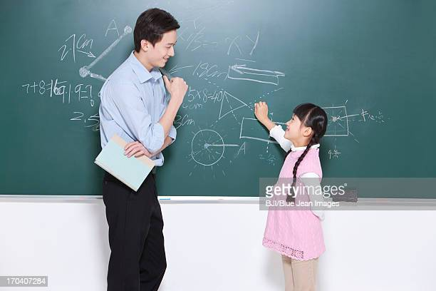 Happy schoolgirl and teacher in classroom, face to face