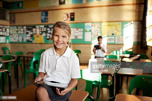 Happy schoolgirl holding tablet