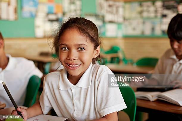 Happy schoolgirl in classroom