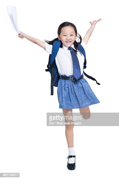 Happy schoolgirl jumping with report card