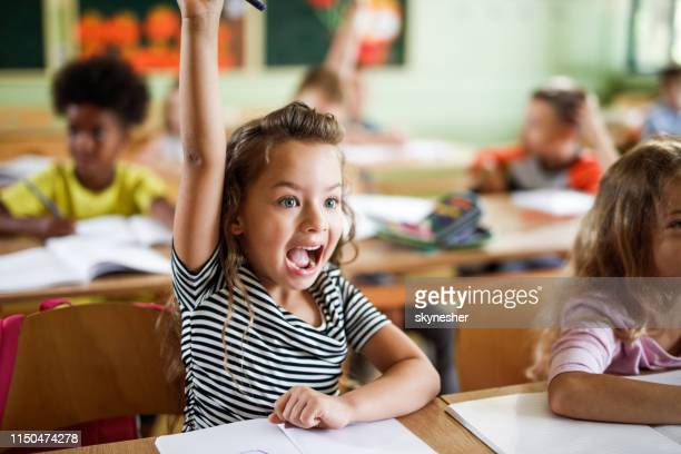 happy schoolgirl raising her hand to answer the question on a class. - asking stock pictures, royalty-free photos & images