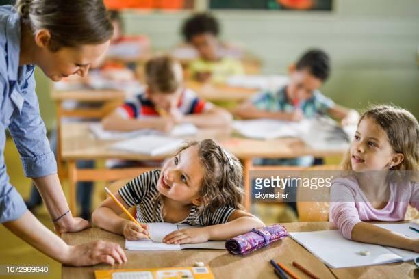 écolière heureux de parler à son enseignante sur une classe à l'école primaire. - enseignante photos et images de collection