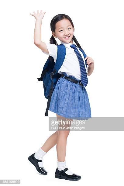 Happy schoolgirl waving